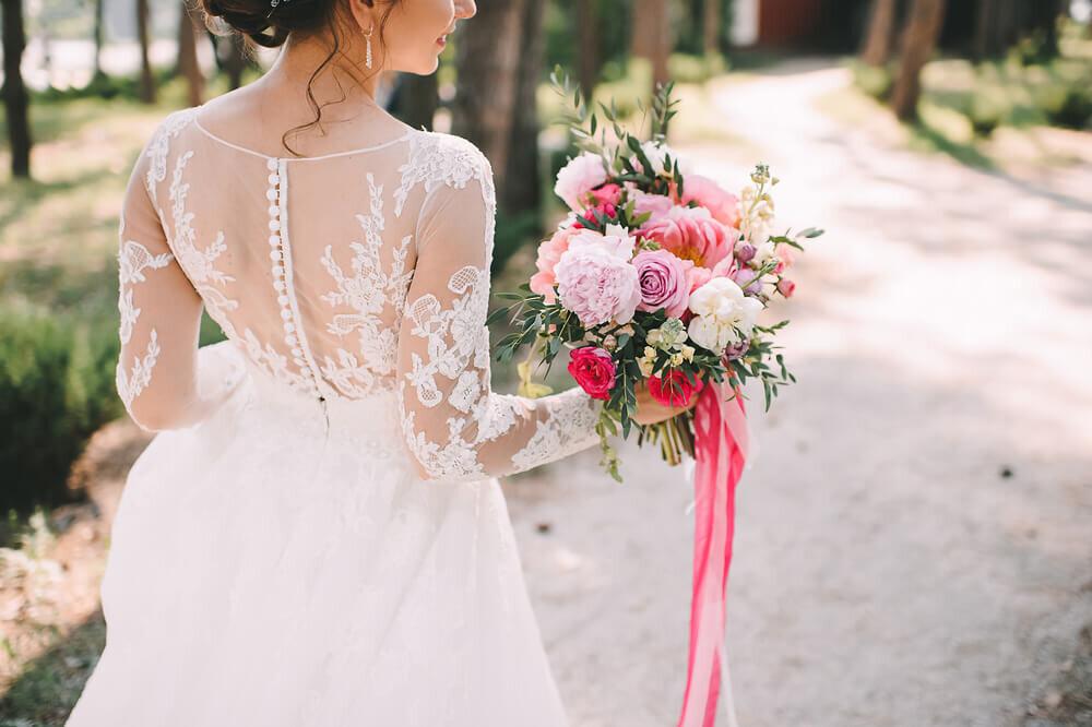 ピンクのリボンを結んだブーケを持つ花嫁の後姿
