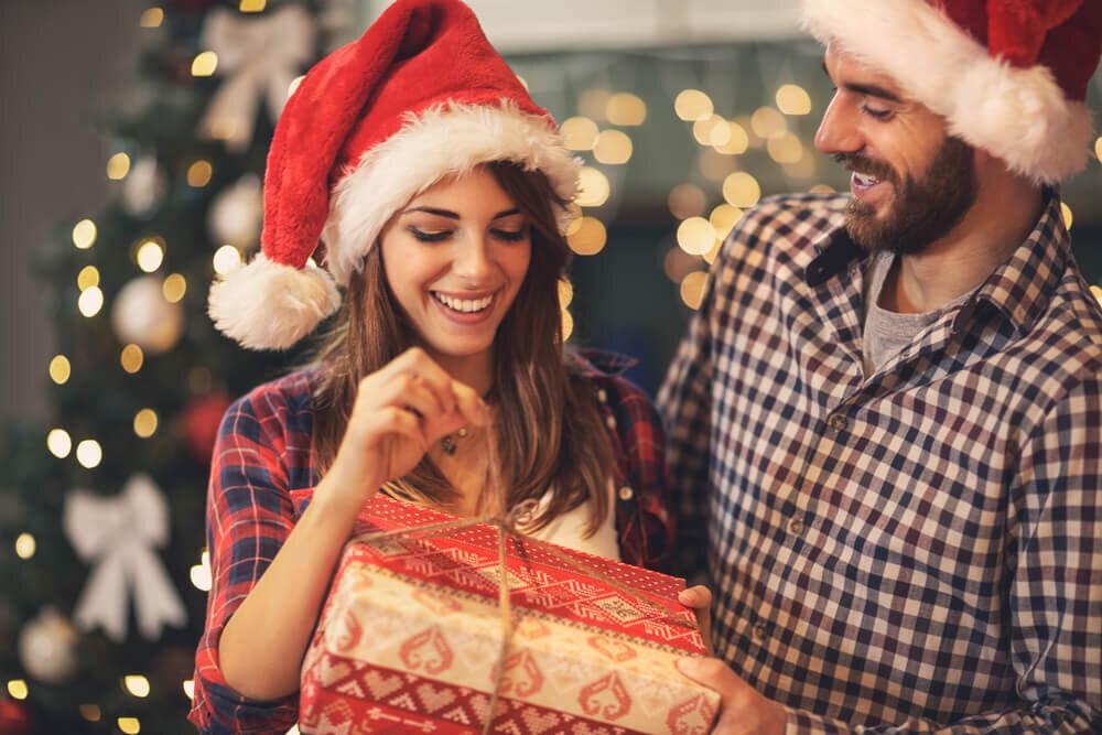 クリスマスプレゼントを開けるカップル