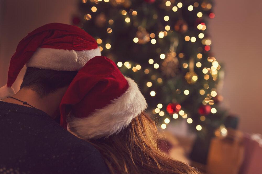 ツリーのそばでクリスマスハットをかぶったカップル