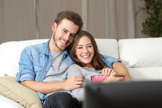 自宅で映画を見るカップル