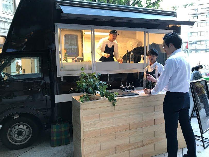 キッチンカー(フードトラック)の前でお客さんと会話をするスタッフ