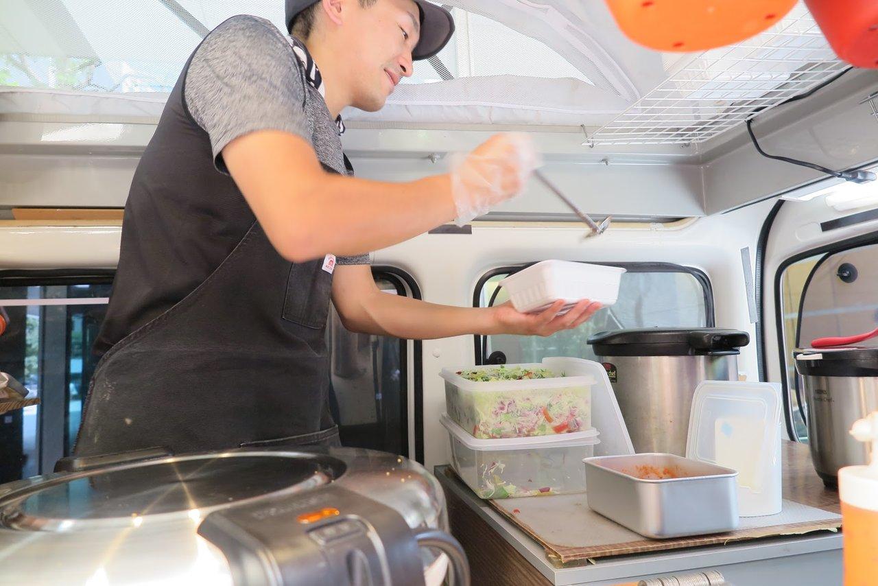 キッチンカー(移動販売車)で調理するオーナー