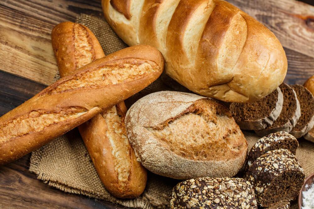 木のテーブルに並んださまざまなパン