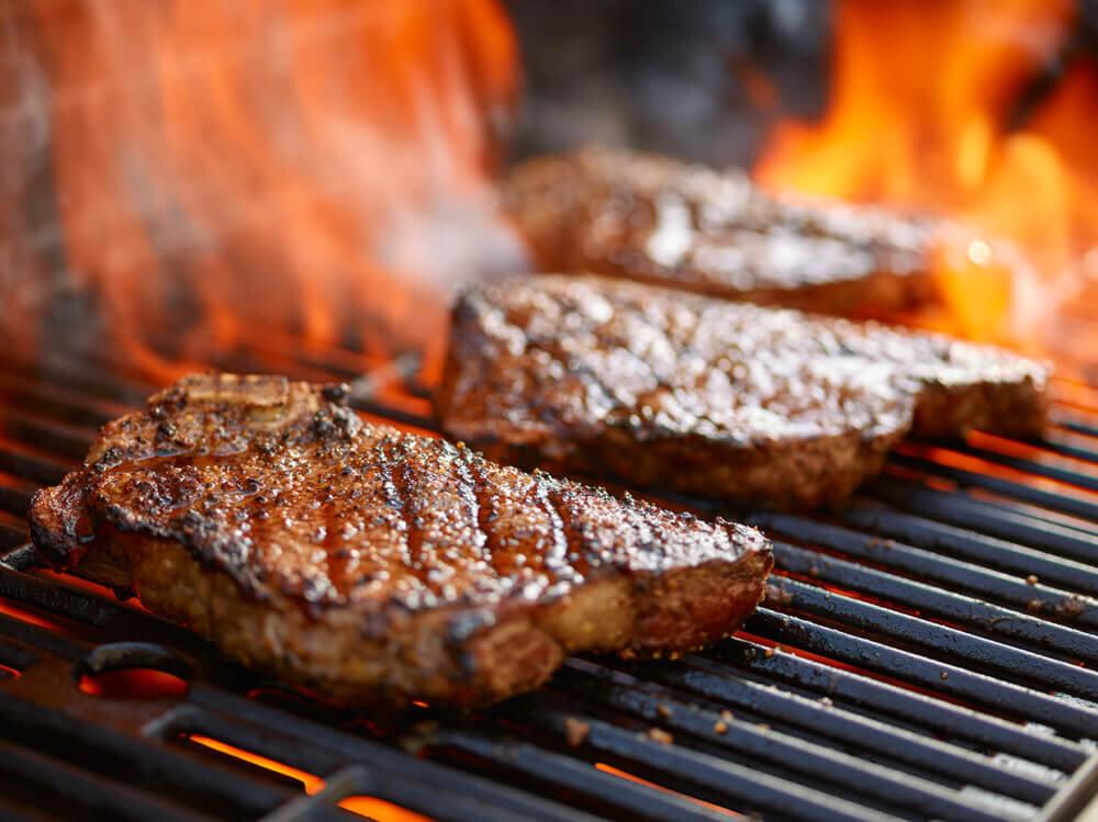 グリルで調理されているステーキ