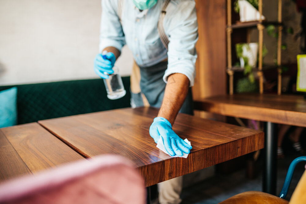 テーブルを消毒する店員