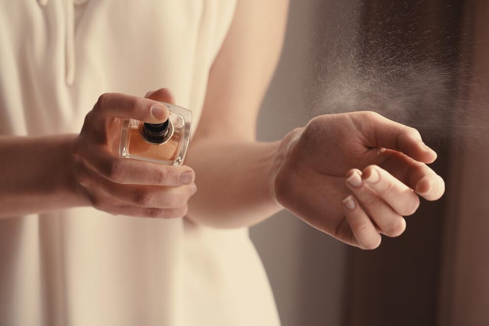 腕に香水をつける女性