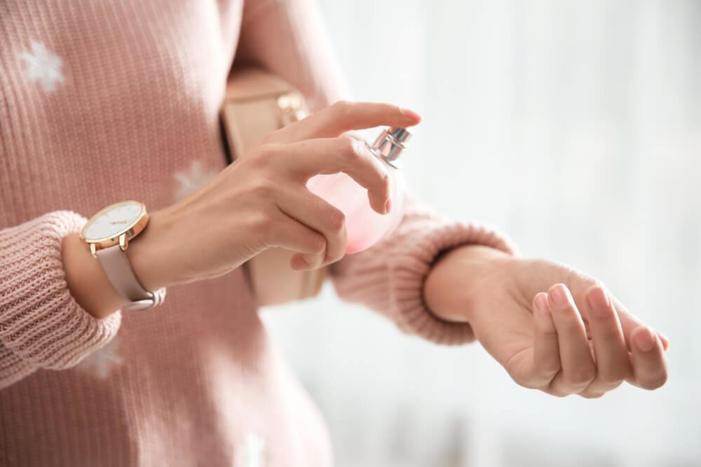 香水をつける冬服の女性