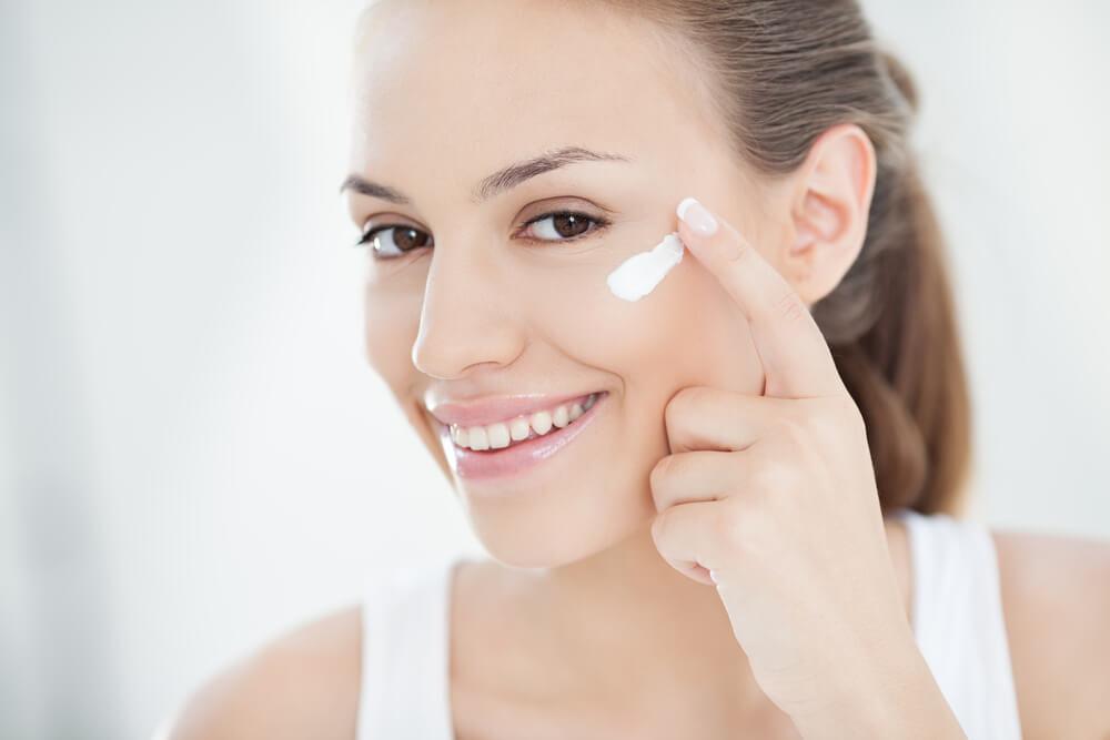 目尻にクリームを塗り微笑む女性