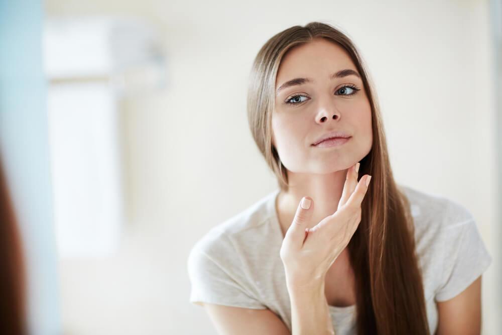 家で鏡を見る若い女性