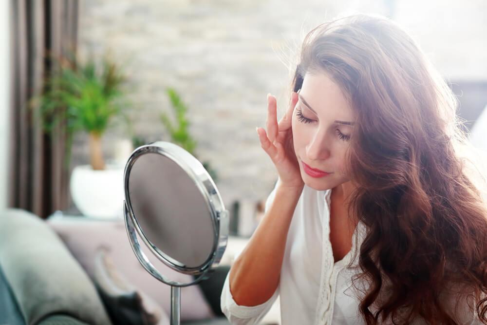 鏡を見つめて悩む女性