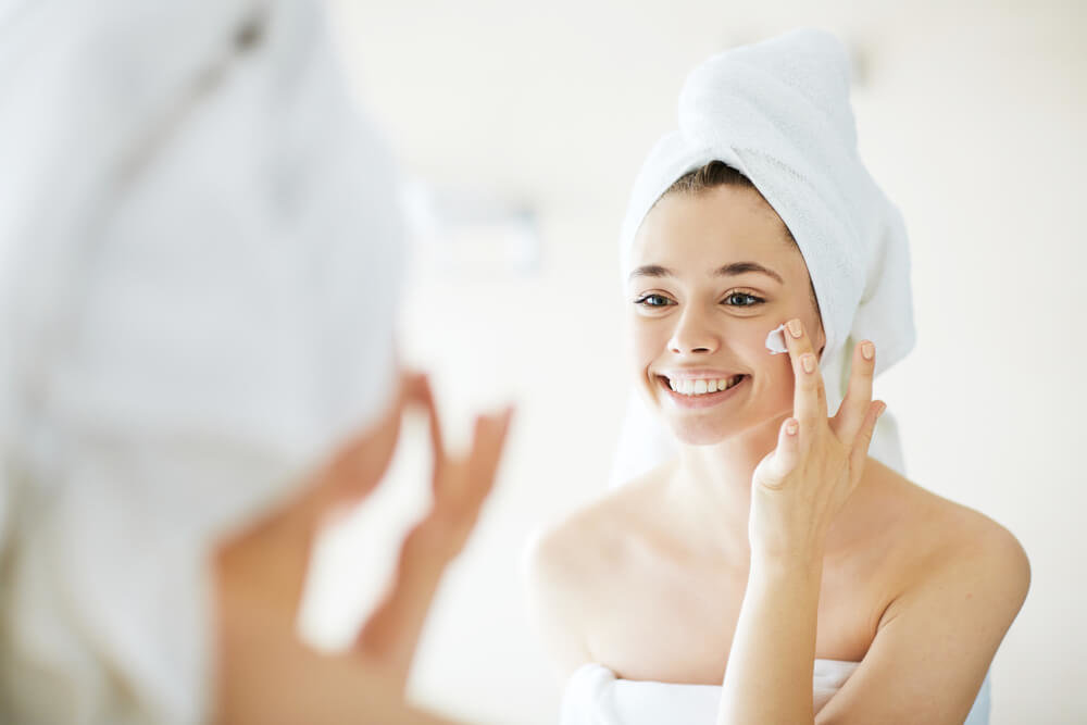 クリームを塗るお風呂上がりの女性