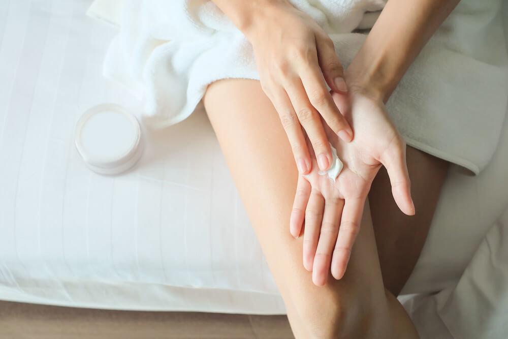 手にクリームを広げる女性