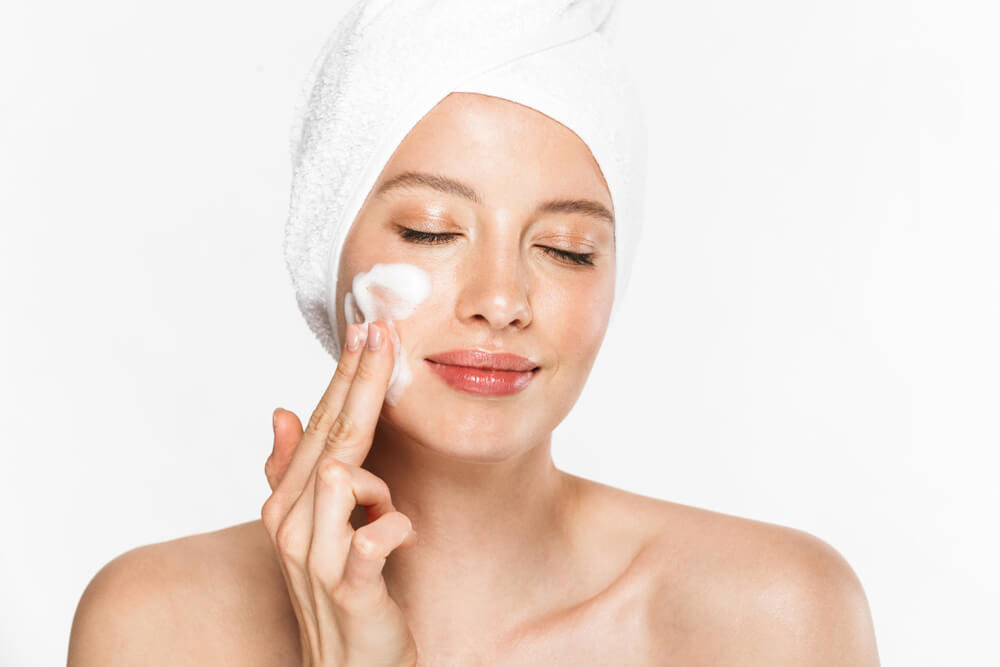 洗顔フォームを顔に塗るタオルの女性