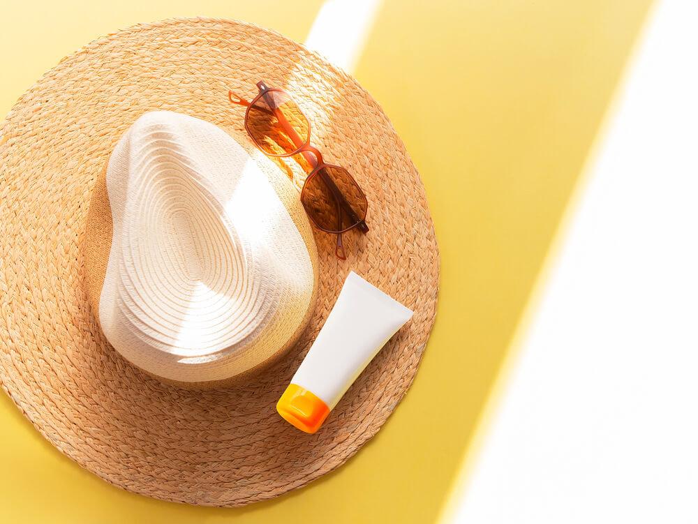 帽子の上にのった日焼け止めとサングラス