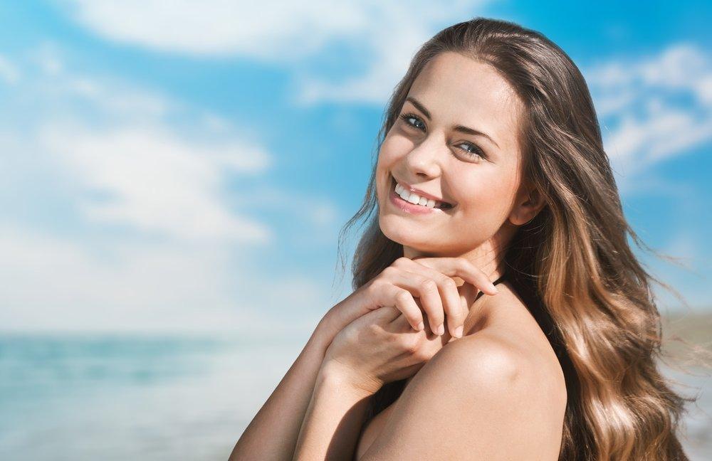 ビーチで明るく微笑む女性