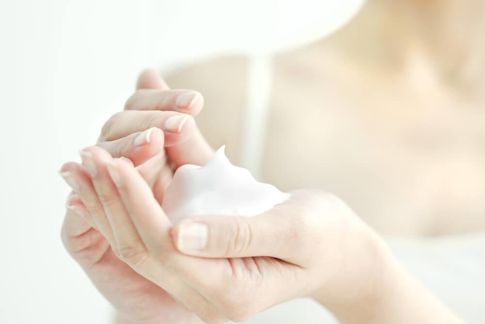 洗顔料を泡立てる女性の手