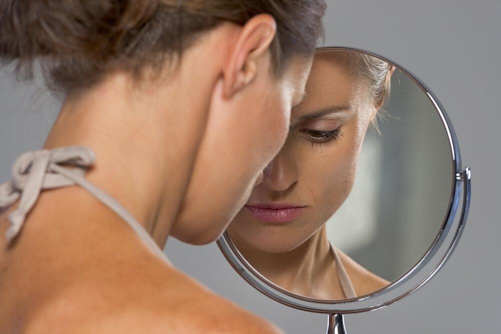 鏡を見て落ち込む女性