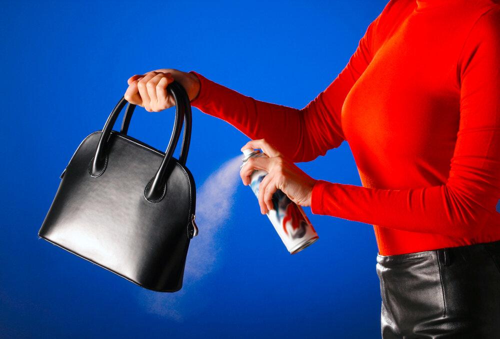 バッグにスプレーをかける女性