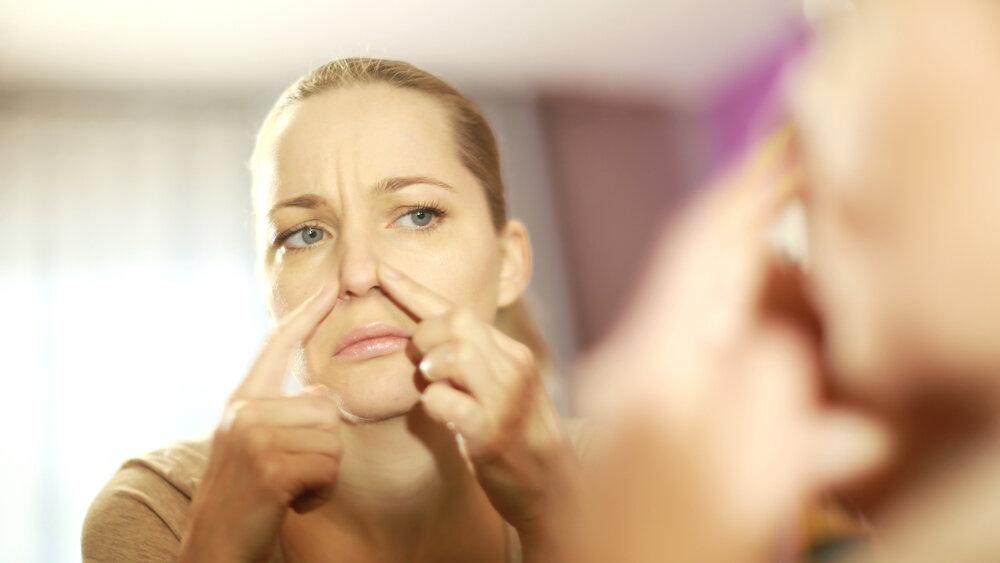 鏡の前で肌をチェックする女性