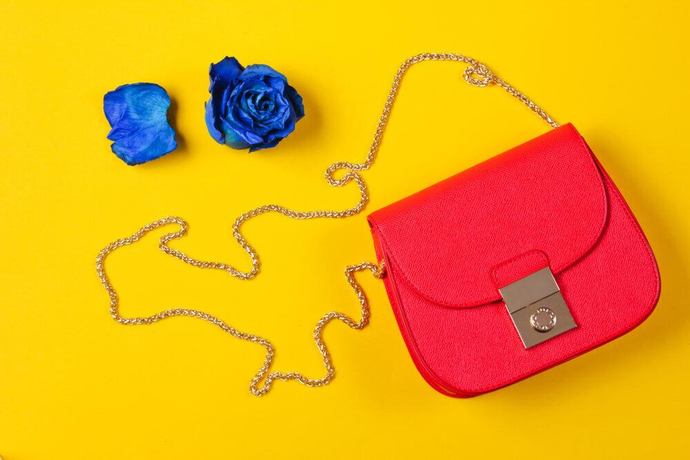 赤いレザーバッグと青いバラ