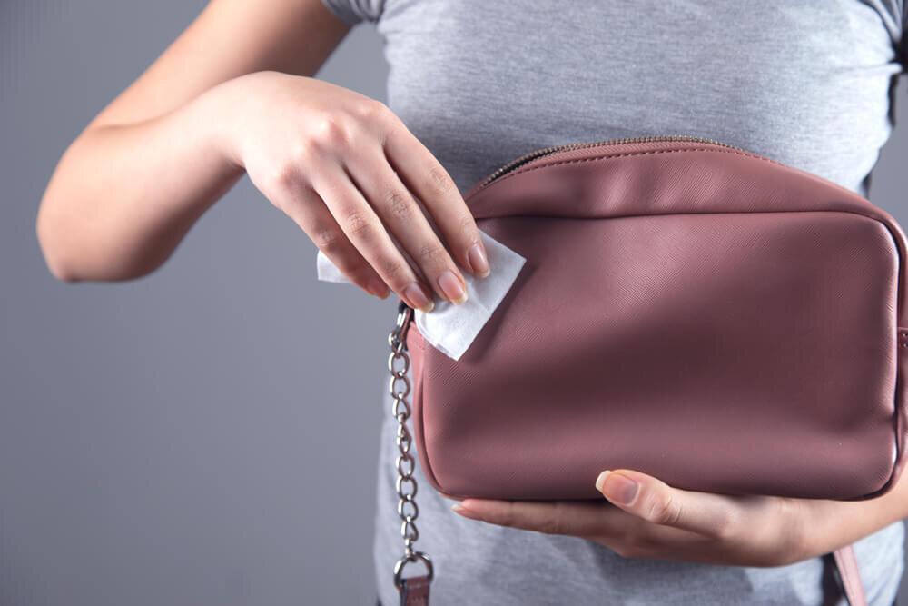 レザーバッグをクリーニングする女性