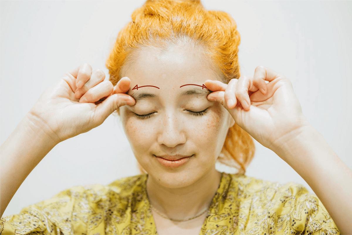 眉頭から繭尻に向かって指を滑らせるマッサージ解説画像