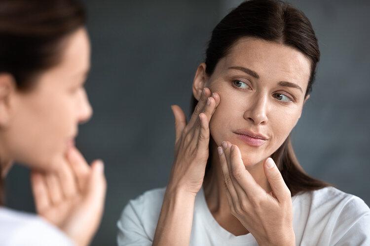頬の状態をチェックする女性