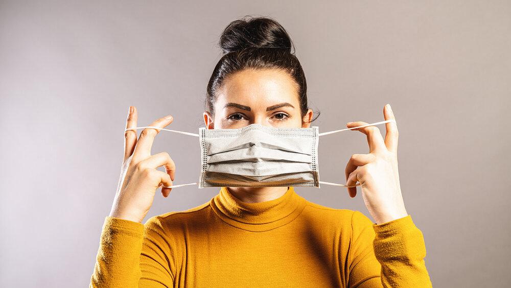 マスクを装着しようとする女性