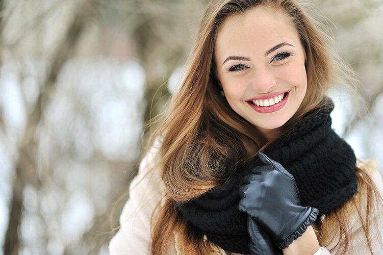 手袋とマフラーをした笑顔の女性