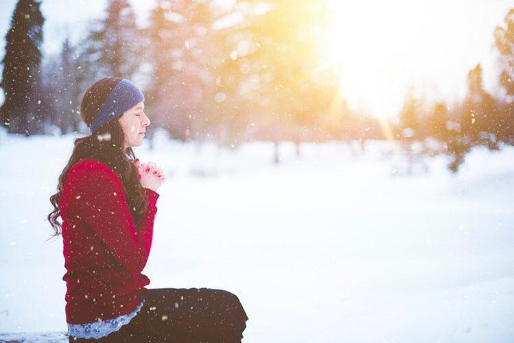雪原で祈る女性
