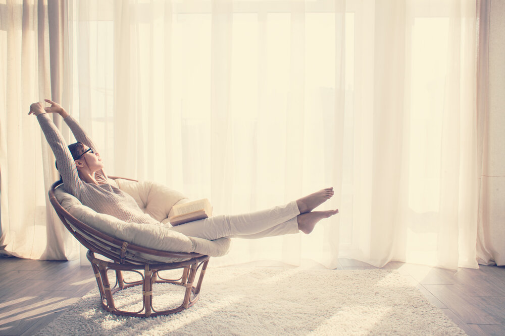 日当たりの良い部屋で伸びをする女性
