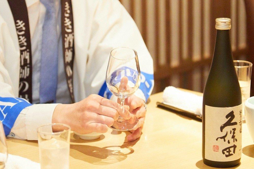 ワイングラスを持つきき酒師の漫才師にほんしゅさん