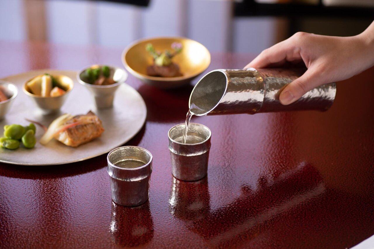 錫製酒器にお酒を注ぐ手