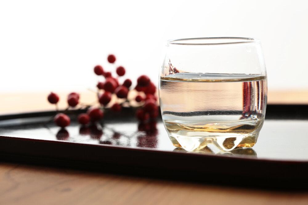 おぼんの上にのったロックグラスに注がれた日本酒