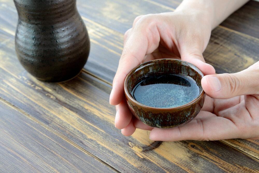 日本酒が入ったおちょこを両手で持つ