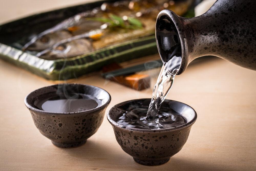 焼き魚とおちょこに注がれる日本酒