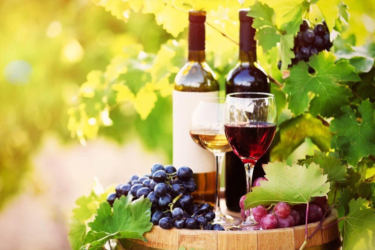 ワイン樽の上に置かれた葡萄とボトルワインとグラスワイン