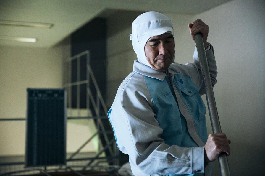 作業着を着て山廃仕込みをする蔵人の男性