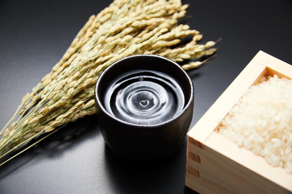 お猪口に入った酒と稲の穂と升に入った米