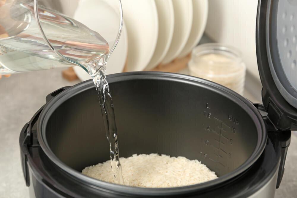 炊飯器に入った米に水を灌ぐ様子