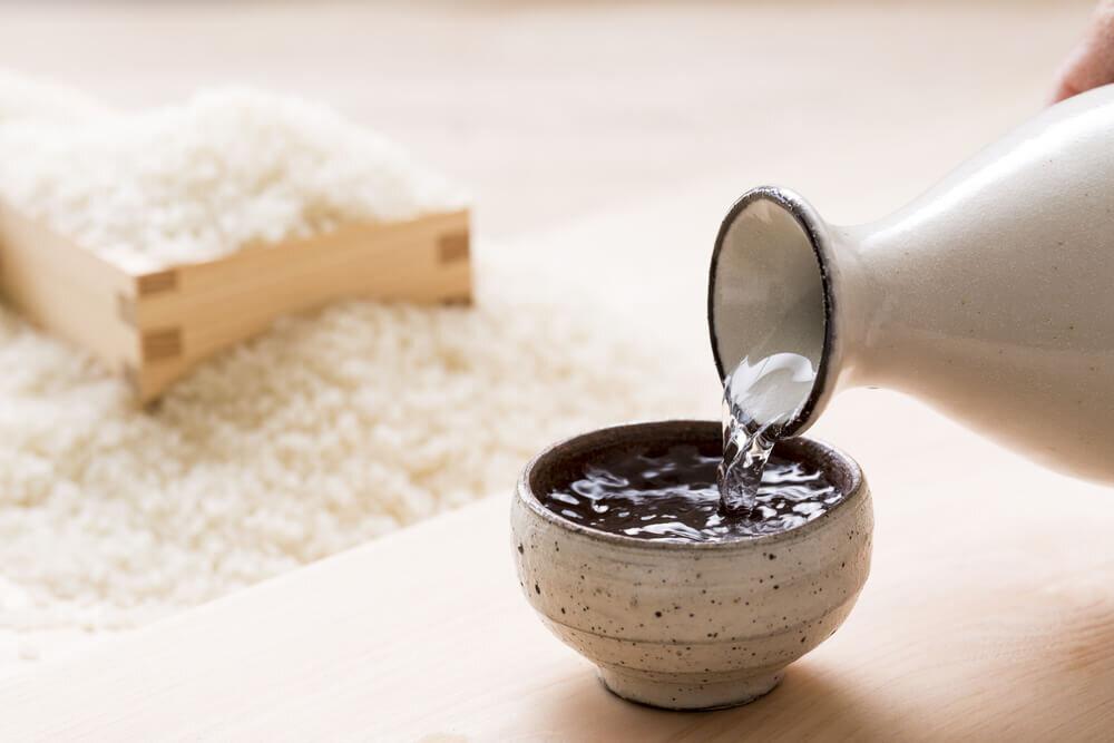 徳利からお猪口に注がれる酒と升に入った米