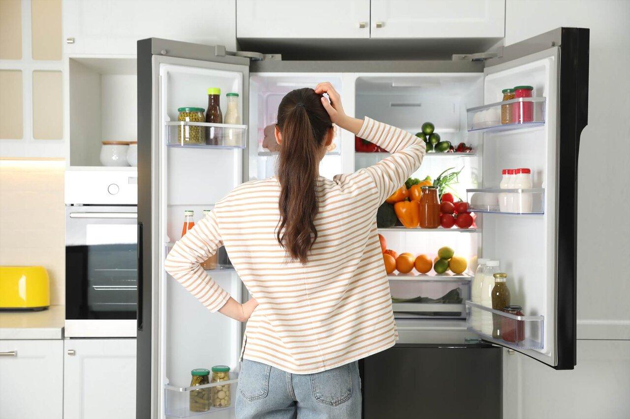 冷蔵庫の前に立つ女性