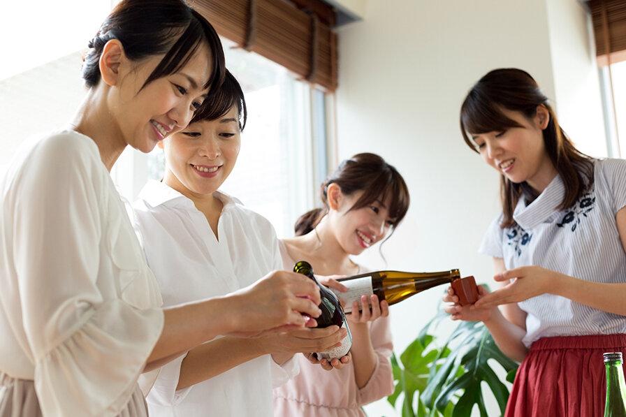 日本酒を注ぐ四人の女性たち