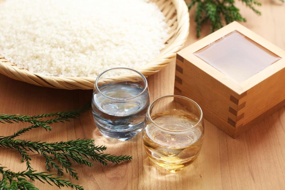 コップや升に入った日本酒と米