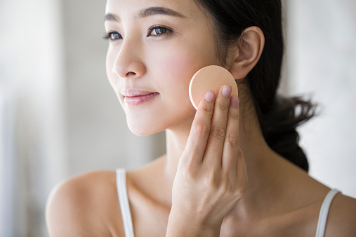 Young woman applying facial...