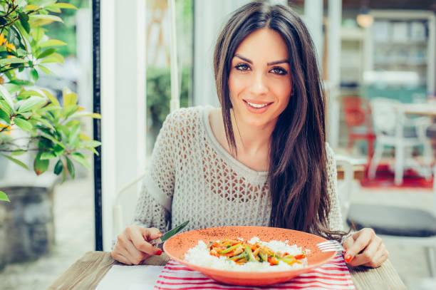 彼女の昼休みを有するレストランでは、中華料理を食べる若い女性