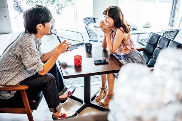 若いアジアのカップル カフェで楽しんで