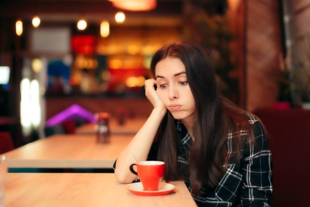 コーヒー ショップで彼女の日付を待っている退屈少女