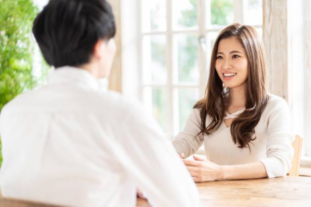 魅力的なアジアのカップルは、リビングルームで話します