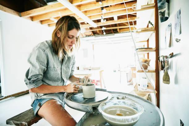 Woman spinning mug on potte...